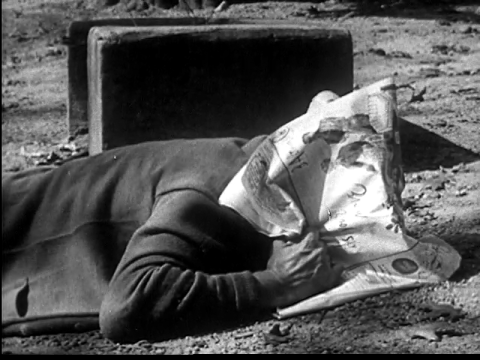 Man hiding under newspaper when the Atomic Bomb strikes, from Duck and Cover (1951)